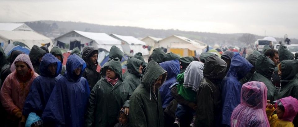 Migrants line up for food during a heavy rainfall at a makeshift camp on the Greek-Macedonian border, near the village of Idomeni