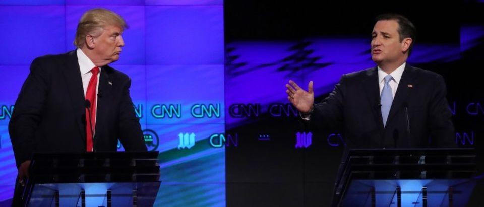 Republican U.S. presidential candidate Trump listens to rival Cruz during the Republican candidates debate in Miami