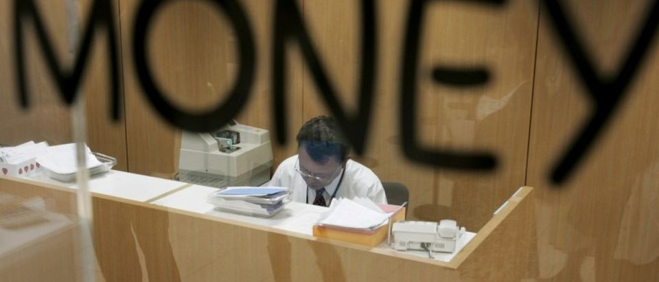 File photo of an employee counting money at foreign currency exchange in Tokyo