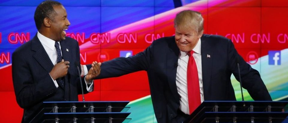 Republican U.S. presidential candidate businessman Trump reacts to a comment from Dr. Carson and reaches over to him in the midst of the Republican presidential debate in Las Vegas