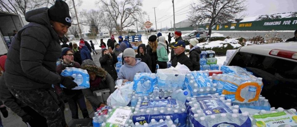 Volunteers distribute bottled water to help combat the effects of the crisis when the city's drinking water became contaminated with dangerously high levels of lead in Flint, Michigan, in this March 5, 2016 file photo. REUTERS/Jim Young Files