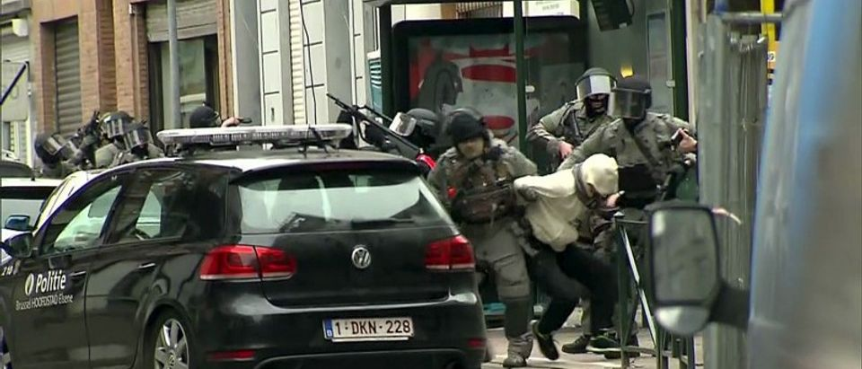 Armed Belgian police apprehend a suspect, in this still image taken from video, in Molenbeek, near Brussels, Belgium