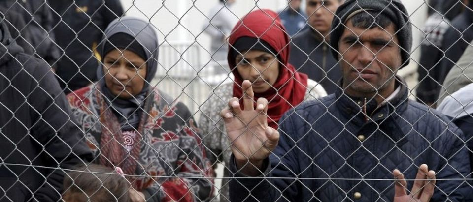 Migrants and refugees stand by a fence at a makeshift camp at the Greek-Macedonian border near the village of Idomeni