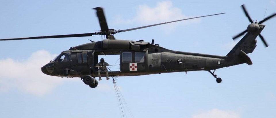 A UH-60 Black Hawk helicopter from the Kansas National Guard carries a water bucket as it prepares to help fight the Anderson Creek wildfire in southern Kansas, March 25, 2016. Picture taken March 25, 2016. REUTERS/Kansas National Guard via social media/Sgt. Zachary Sheely/Handout via Reuters