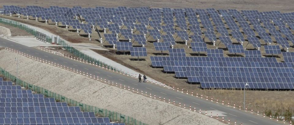 File picture of people walking past the solar panels at a wind and solar energy storage and transmission power station in Zhangjiakou