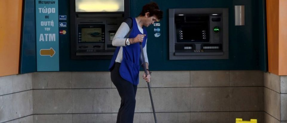 A cleaning lady mops the floor in front of an ATM outside a branch of the Bank of Cyprus in Nicosia, Cyprus March 7, 2016. REUTERS/Yiannis Kourtoglou