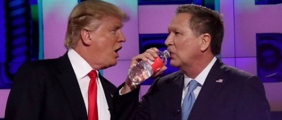 Republican presidential candidate Donald Trump talks with rival John Kasich during a commercial break in the midst of the debate sponsored by CNN at the University of Miami in Miami, March 10
