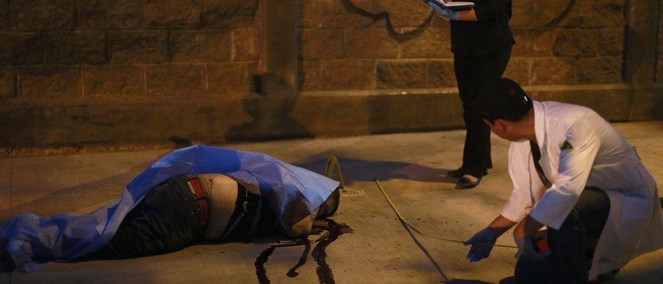 Forensic investigators work at a crime scene where a man was shot dead near a school in Chilpancingo