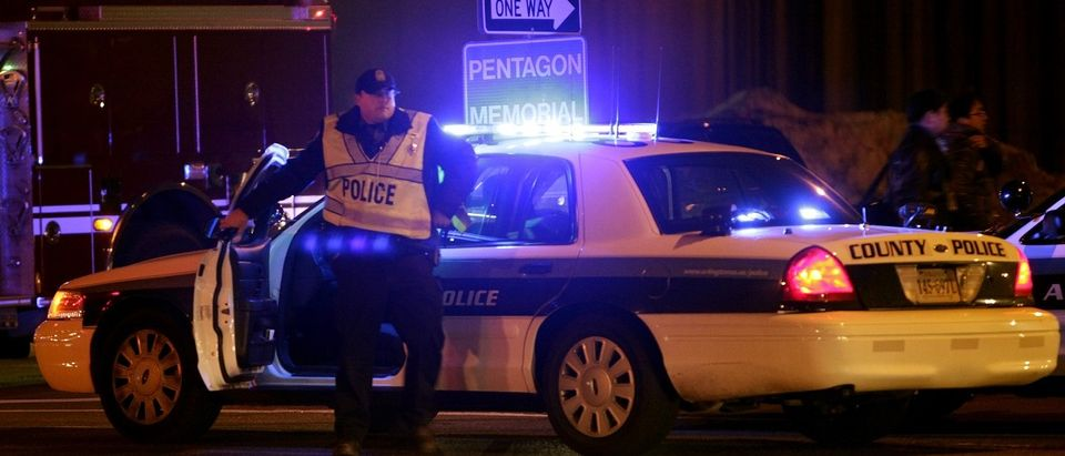 A police officer gets out of his car at a roadblock around the Pentagon in Washington March 4, 2010. Two Pentagon security officers were wounded on Thursday evening when a gunman shot at them in the giant office building's main entrance to the Metro commuter rail system, Pentagon officials said. REUTERS/Yuri Gripas