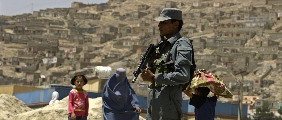 Afghan policeman keeps watch as people walk on a street in Kabul