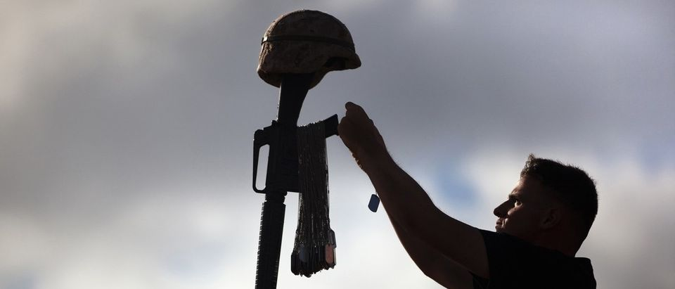 U.S. Marine Corps Lance Cpl. Niro places the dog tag of a fallen Marine on a battlefield cross at Marine Corps Base Hawaii