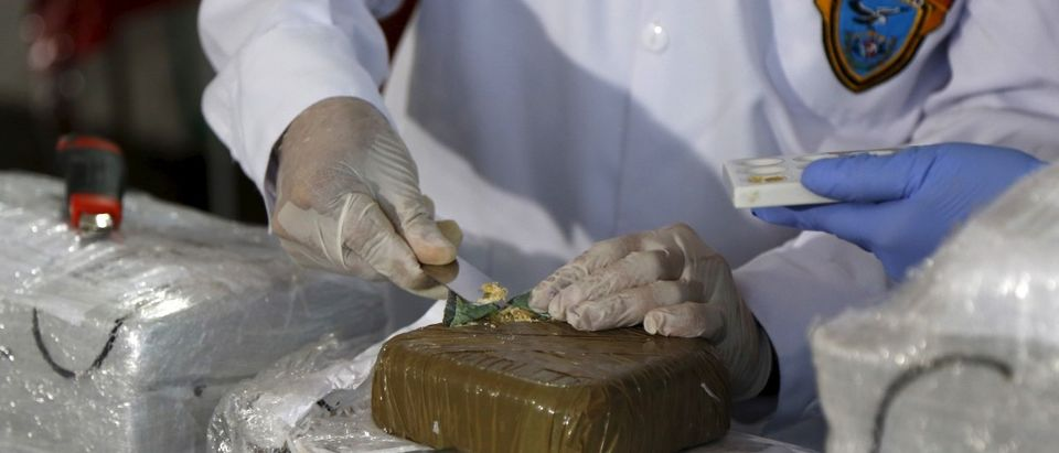 An anti-narcotics police chemist tests cocaine from a seized brick from an operation last week during a media conference at the police headquarters in Lima February 29, 2016. Police seized 285.6 kilograms of cocaine from the operation in Sandia province, Puno region, and announced the arrest of one man identified as Edwin Lens Sipiri, 25, from Bolivia, according to the police. REUTERS/Janine Costa - RTS8M23