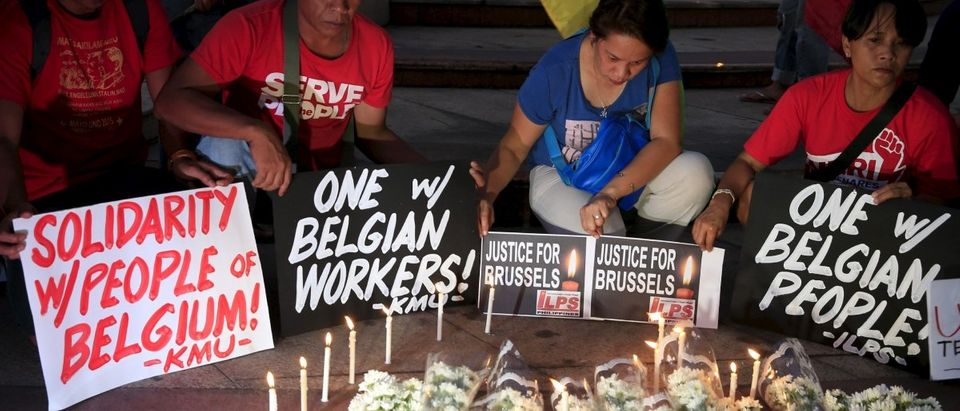 "Activists lights candles and offers flowers asking for the ""Justice for Brussels"" during a memorial event along a main street in Quezon city, metro Manila"