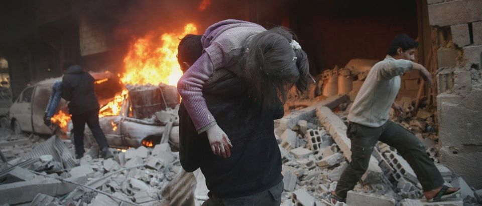 A man carries an injured child amidst rubble in a site damaged from what activists said was shelling by forces loyal to Assad in the town of Douma