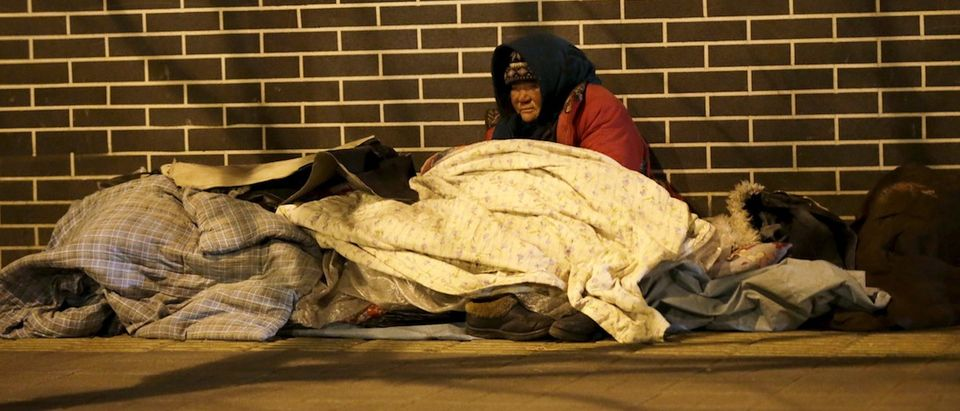 A homeless woman is seen on a cold winter night