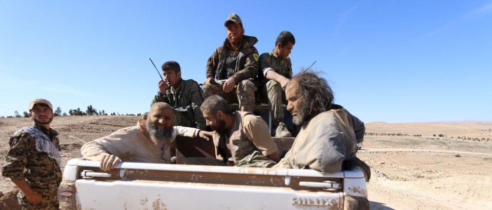 Three men that Democratic Forces of Syria fighters claimed were Islamic State fighters sit on a pick-up truck while being held as prisoners near al-Shadadi town