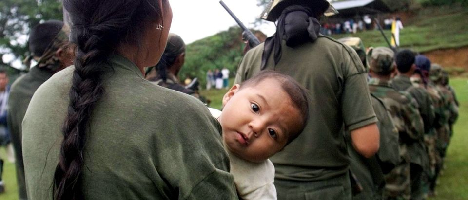 - PHOTO TAKEN 06DEC03 - A peasant member of a self-defense group holds her baby before surrender her..
