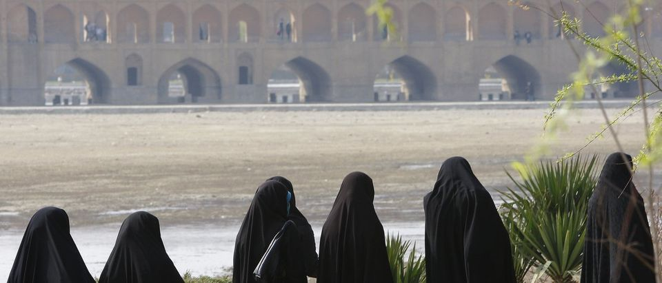 Women walk near arches of Sio-se Pol over Zayand-e Rud river in Isfahan