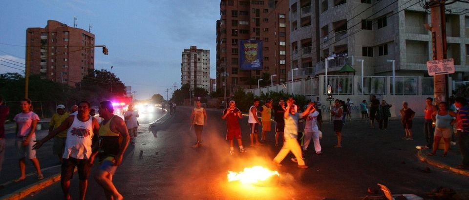 People burn a tyre as they block a road in protest after a large blackout in the western city of Maracaibo