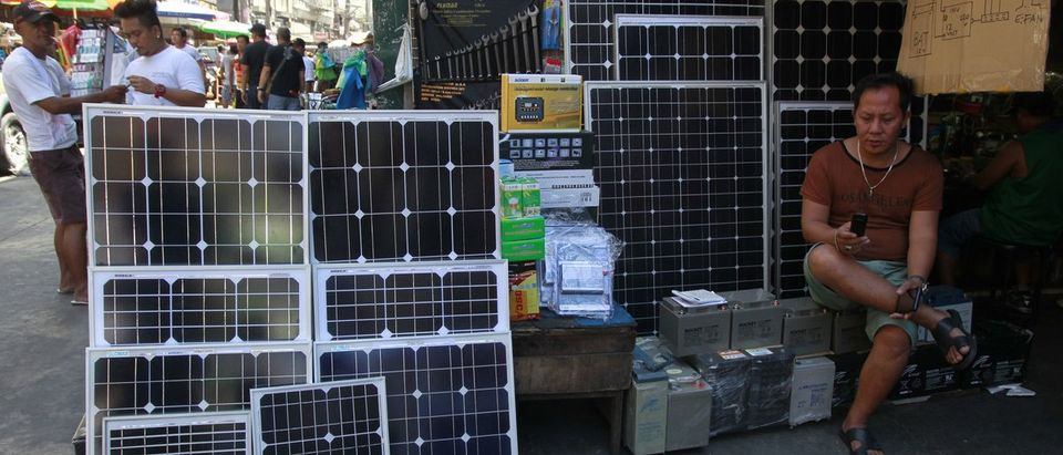A worker waits for customers beside solar panels which he sells along a main road in Manila