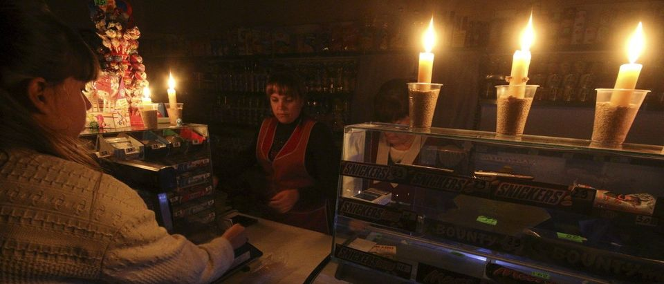 A customer visits a grocery lit with candles due to a power cut, in Simferopol, Crimea
