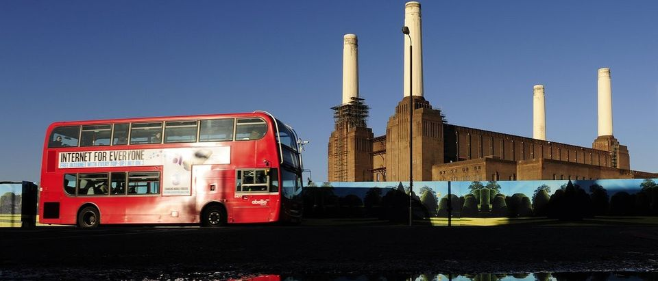 Battersea Power Station is seen reflected in water in west London