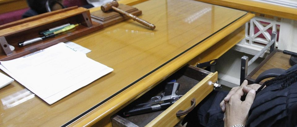 Santiago, a lower court judge in Manila, keeps his drawer open containing service pistol while hearing case at city hall in Manila