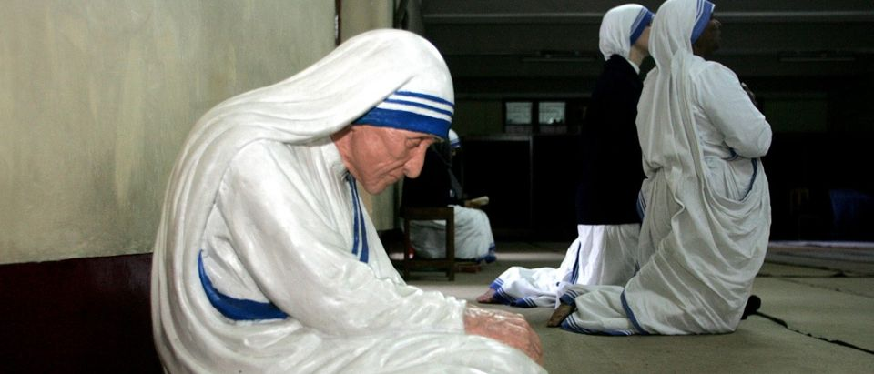 Catholic nuns from the Missionaries of Charity kneel as they pray beside a statue of Mother Teresa in ...