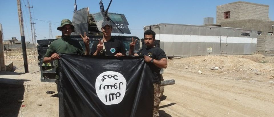 Iraqi security forces stand with an Islamic State flag which they pulled down in the town of Hit in Anbar province