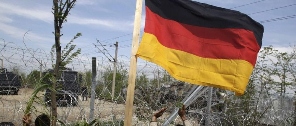 Migrant carries a German flag in front of Macedonian police as they stand guard behind a fence near a makeshift camp at the Greek-Macedonian border near the village of Idomeni