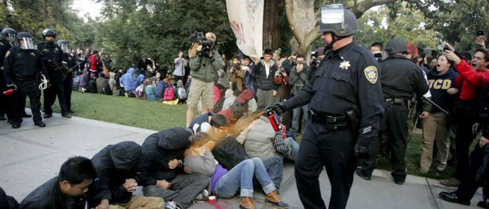 """File photo of University of California Davis police officer pepper-spraying students during their sit-in at an """"Occupy UCD"""" demonstration in Davis"""