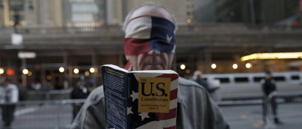 A blindfolded demonstrator holds up a copy of the United States Constitution while protesting against the Republican U.S. presidential candidate Donald Trump in midtown Manhattan in New York City