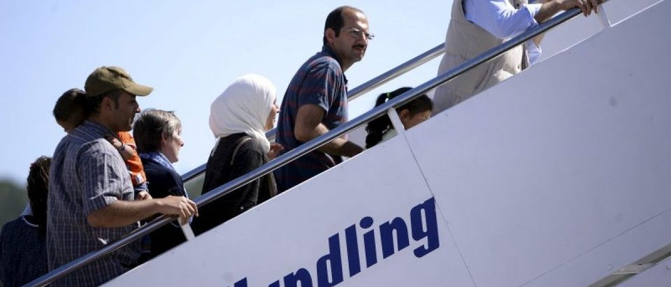 A group of Syrian refugees board a plane with Pope Francis at the airport of Mytilene, in the Greek island of Lesbos