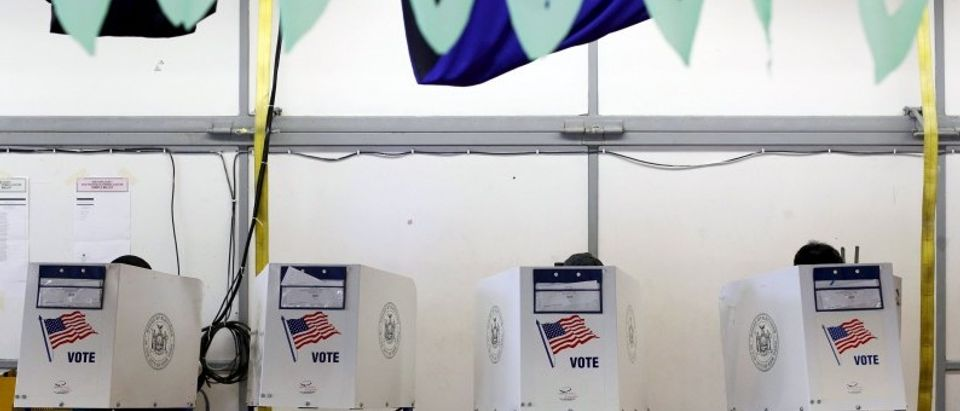 Voters use booths located under stage props at the polling center at the James Weldon Johnson Community Center during the New York primary elections in the East Harlem neighborhood of New York City, U.S.
