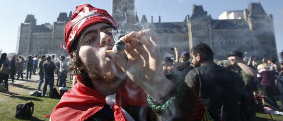A man smokes marijuana during an annual 4/20 rally on Parliament Hill in Ottawa