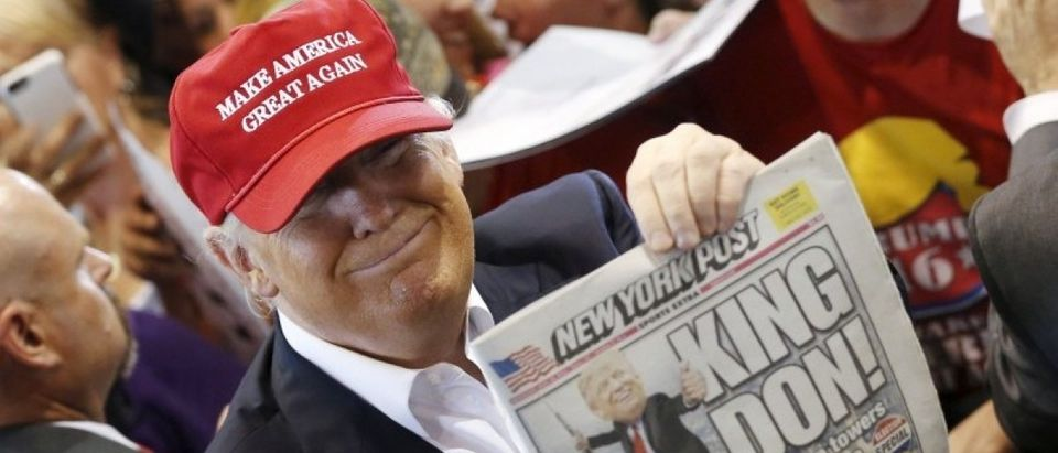 Trump holds up the front page of the New York Post as he signs autographs at a rally with supporters in Harrington, Delaware