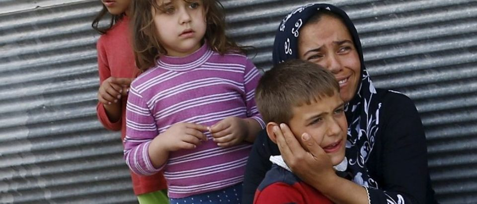 A mother and her children react after two rockets hit the Turkish town of Kilis
