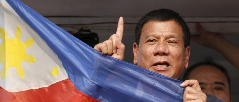 """Presidential candidate Rodrigo """"Digong"""" Duterte holds the national flag during election campaigning for May 2016 national elections in Malabon, Metro Manila"""
