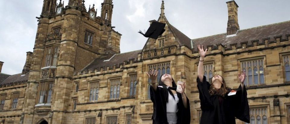 University students toss their graduation hats into the air for friends and family to take photos following their graduation ceremony at University of Sydney in Sydney, Australia, April 22, 2016. REUTERS/Jason Reed