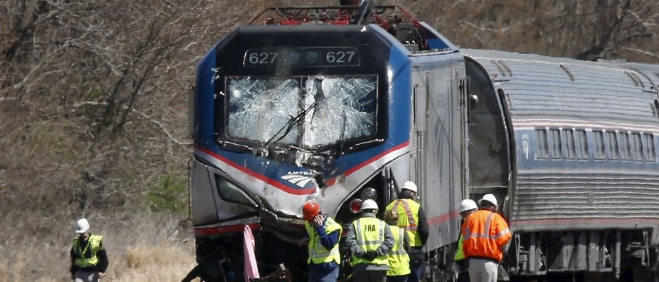 Emergency personnel examine the scene after an Amtrak passenger train struck a backhoe, killing two people, in Chester, Pennsylvania