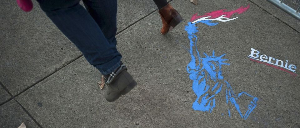 A pedestrian walks past a sidewalk chalk illustration supporting U.S. Democratic presidential candidate Bernie Sanders in Des Moines, Iowa