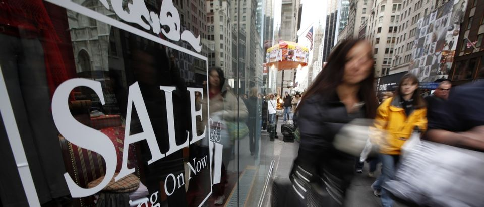 Shoppers walk down Fifth Avenue past a sale sign in the window of a Brooks Brothers store in New York