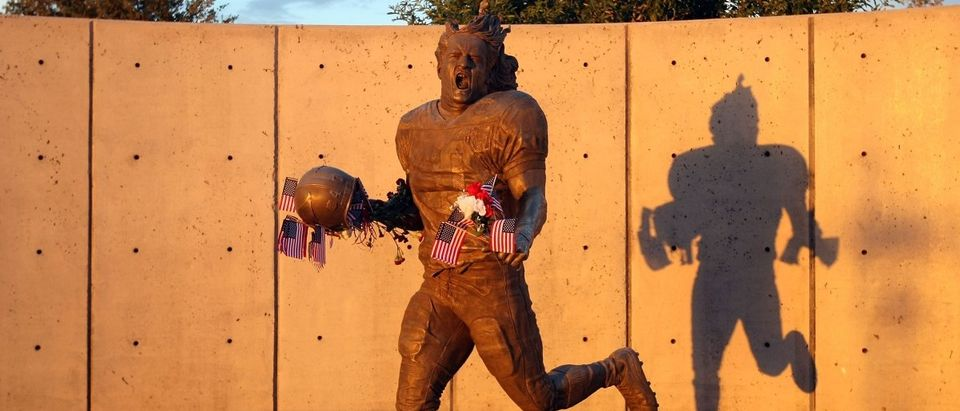 Fans adorn the Pat Tillman statue with American flags in honor of the 10 year anniversary of the 9/11 attacks following the NFL season opening game between the Carolina Panthers and the Arizona Cardinals at the University of Phoenix Stadium on September 11, 2011 in Glendale, Arizona