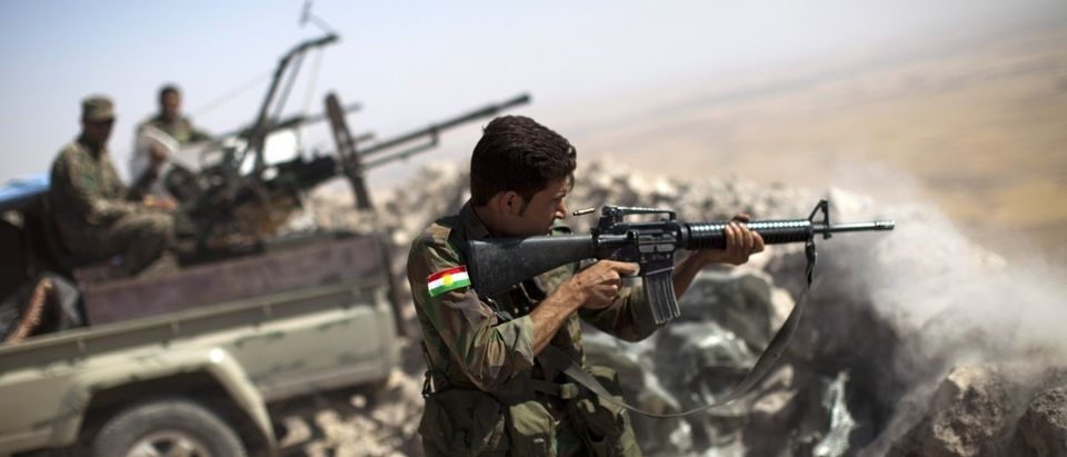 An Iraqi Kurdish Peshmerga fighter fires at Islamic-State (IS) militant positions, from his position on the top of Mount Zardak, a strategic point taken 3 days ago, about 25 kilometres east of Mosul on September 9,2014. (JM LOPEZ/AFP/Getty Images)