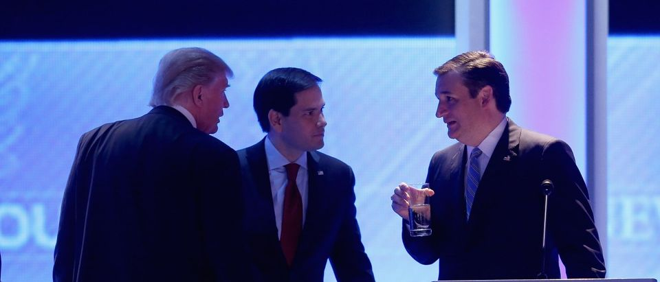 Republican presidential candidates Donald Trump, Sen. Marco Rubio and Sen. Ted Cruz talk during a commercial break in the Republican presidential debate at St. Anselm College February 6, 2016 in Manchester