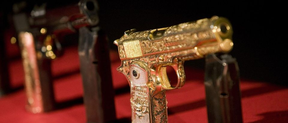 Pistols decorated with gold seized from suspected drug gang hitmen are displayed to the media at a military base on the outskirts of Monterrey
