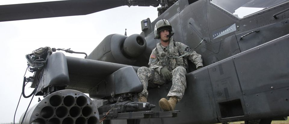 A US soldier sits on an AH-64D Apache attack helicopter as he waits for a live-fire drill at a US air base in Gunsan