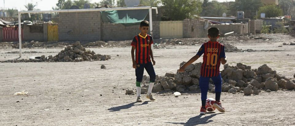 Boys play soccer in an abandoned soccer pitch in Baquba