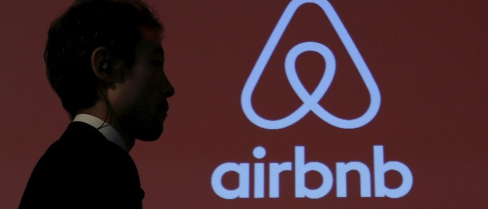 A man walks past a logo of Airbnb after a news conference in Tokyo
