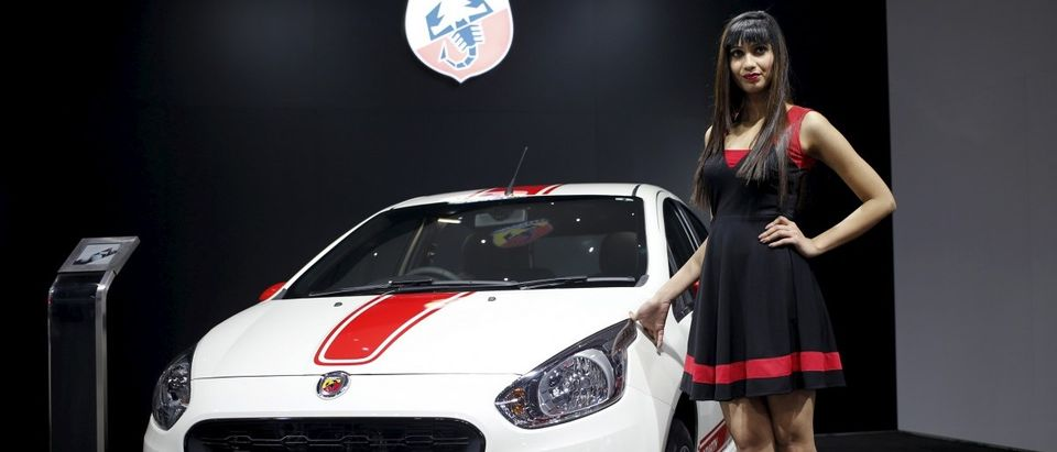 A model poses next to a Fiat Abarth car on display at the Indian Auto Expo in Greater Noida
